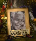 This picture shows a framed image of former South African president Nelson Mandela as people pay tributes following his death, in Johannesburg on December 6, 2013. Nelson Mandela, the revered icon of South Africa's anti-apartheid struggle and a towering figure of 20th century politics, died on December 5 aged 95.  AFP PHOTO / ALEXANDER JOE